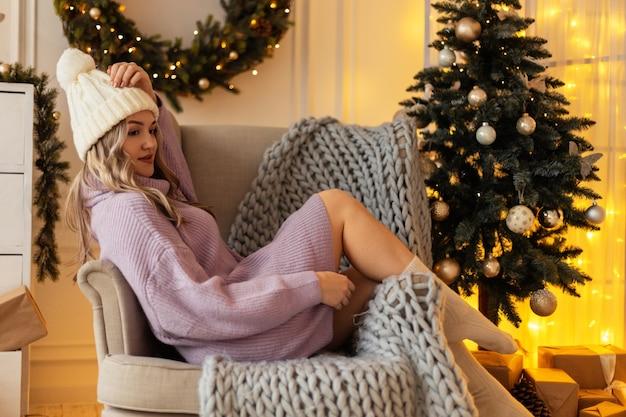 Bella ragazza con un cappello lavorato a maglia in un maglione vintage e calzini si siede e riposa su una poltrona con un plaid a maglia vicino all'albero di natale e ai regali. buon natale e vacanze invernali