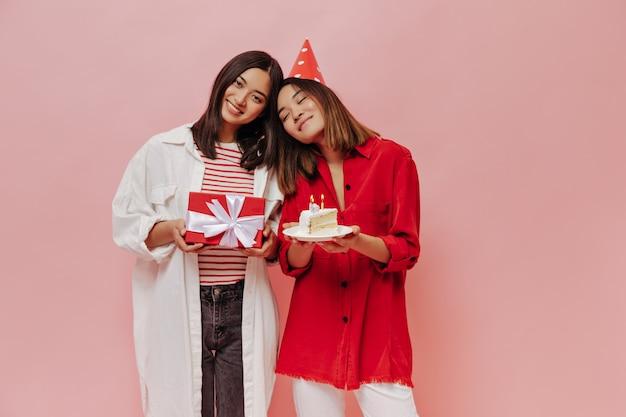 Belle ragazze in lunghe camicie oversize festeggiano il compleanno sulla parete rosa. la donna con il cappello da festa rosso tiene la torta di compleanno