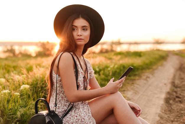 Piuttosto giovane donna all'aperto nel campo utilizzando il telefono cellulare che indossa il cappello.