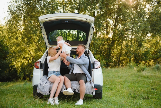 La coppia sposata abbastanza giovane e la loro figlia stanno riposando nella natura. la donna e la ragazza sono sedute sul bagagliaio dell'auto aperto.