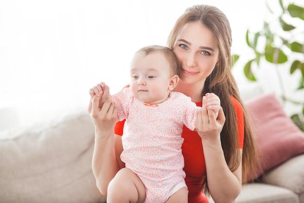 Madre abbastanza giovane che tiene la sua neonata