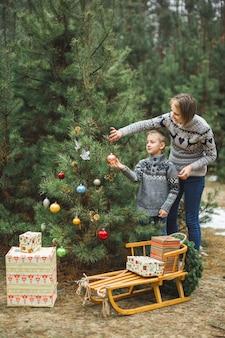 Madre abbastanza giovane e figlio che decorano un albero di natale nella foresta di inverno all'aperto