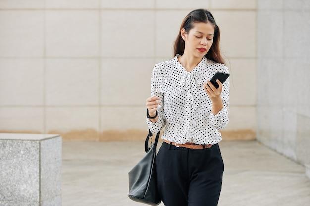Piuttosto giovane giovane imprenditrice multietnica in camicetta a pois camminare all'aperto anc leggendo il messaggio di testo sullo smartphone