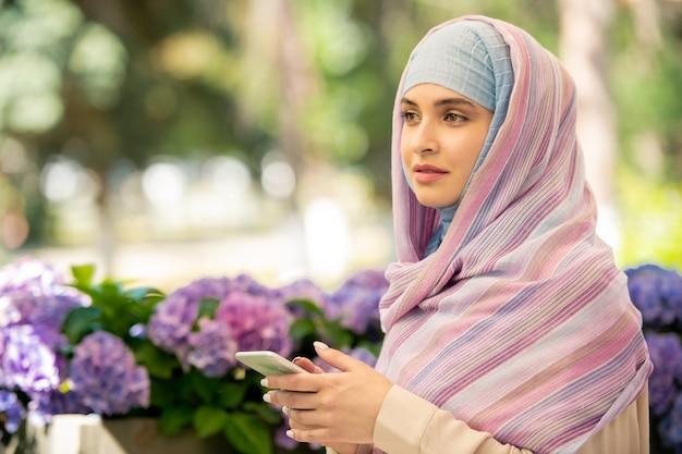 Donna musulmana abbastanza giovane in hijab che scorre nello smartphone mentre trascorre il tempo all'aperto