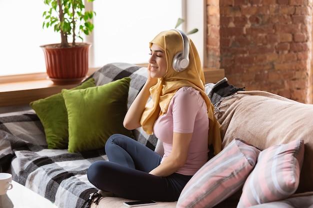 Una bella giovane donna musulmana a casa durante la quarantena e l'autoisolamento. modello femminile arabo che trascorre del tempo utile per essere isolato. concetto di assistenza sanitaria, comunicazione, educazione durante la pandemia.