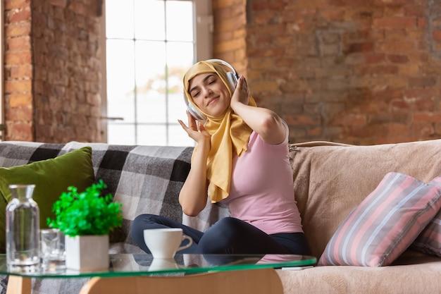 Una bella giovane donna musulmana a casa durante la quarantena e l'autoisolamento