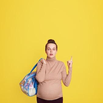Piuttosto giovane donna incinta che punta con il dito indice in su, avendo grande, posa isolata sopra la parete gialla, gestante con roba del bambino con espressione facciale stupita