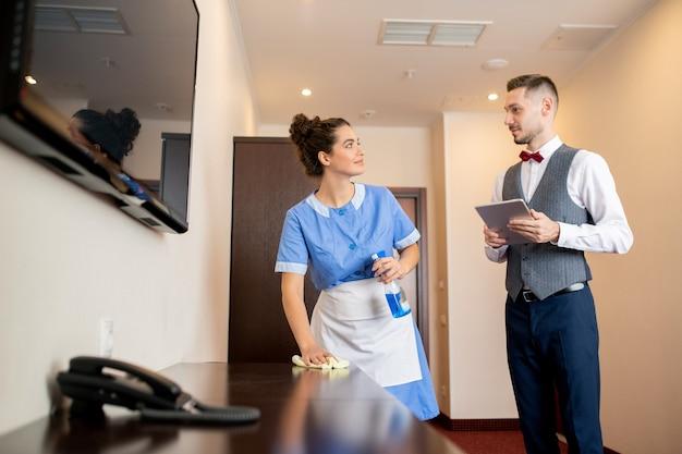 Piuttosto giovane cameriera di stanza che pulisce mobili in legno con detersivo e spolverino mentre parla con il portiere nel corridoio dell'hotel