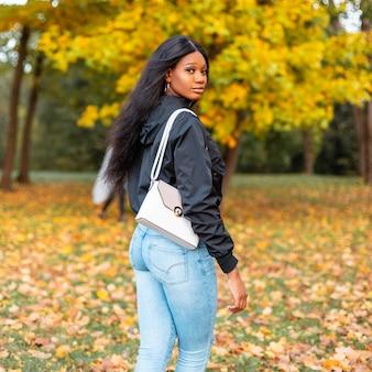 Donna afroamericana sexy abbastanza giovane in vestiti di moda con giacca casual, jeans blu e borsa alla moda nel parco autunnale con foglie di autunno colorate di giallo