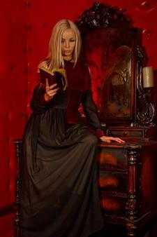 Bella giovane bionda sexy in abito gotico all'interno della stanza rossa medievale con un vecchio specchio legge la bibbia e mostra le emozioni. immagine della regina dell'orrore di halloween. copia spazio per testo o logo