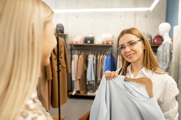 Piuttosto giovane commessa che guarda il cliente davanti a lei mentre mostra una nuova felpa bianca e lo consiglia alla giovane donna
