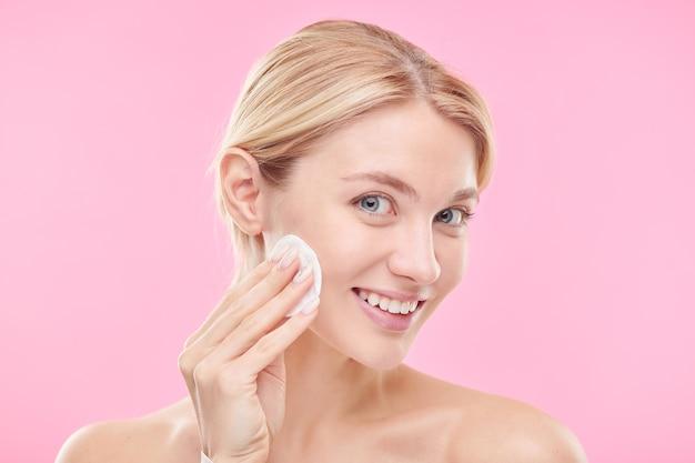 Piuttosto giovane donna sorridente con un batuffolo di cotone che applica toner o acqua micellare mentre si pulisce il viso contro il muro rosa