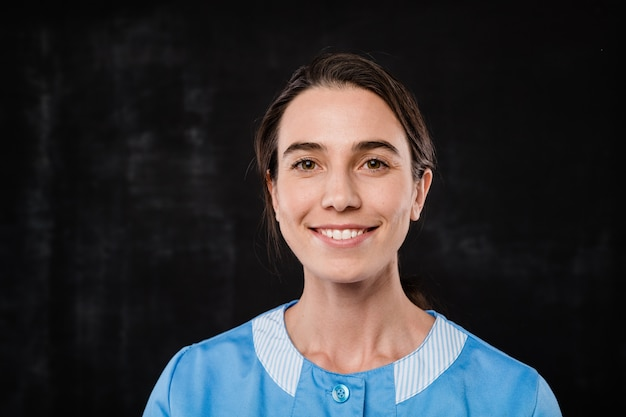 Piuttosto giovane sorridente personale di servizio in camera d'albergo in uniforme blu in piedi davanti alla telecamera su sfondo nero