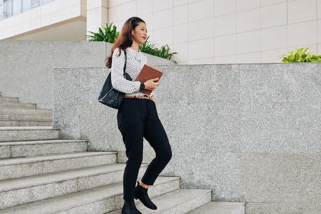 Studente universitario multietnico sorridente abbastanza giovane che cammina giù per le scale quando si affretta alle lezioni