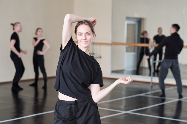 Piuttosto giovane studente del corso di danza classica moderna in activewear nero in piedi mentre fa esercizio
