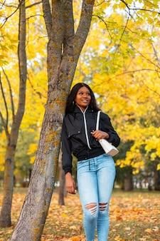 Donna africana alla moda abbastanza giovane con un sorriso in una giacca casual nera alla moda con jeans e una borsa vicino a un albero in un parco autunnale con fogliame giallo brillante