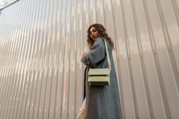 Piuttosto giovane donna modello elegante con i capelli ricci in un cappotto verde di moda con una borsa da donna cammina vicino a un muro di metallo sulla strada. moda e stile casual autunnale femminile