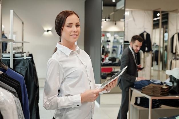Consulente di successo abbastanza giovane della boutique che utilizza la tavoletta digitale davanti alla macchina fotografica mentre inserisce le nuove informazioni