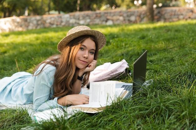 Ragazza adolescente abbastanza giovane che pone su un'erba al parco