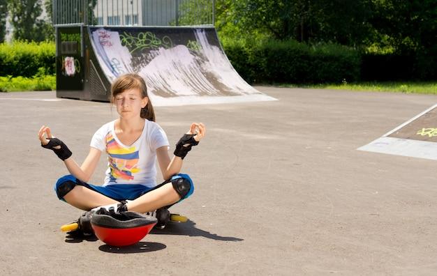 Piuttosto giovane ragazza adolescente in rollerblades seduto meditando sull'asfalto