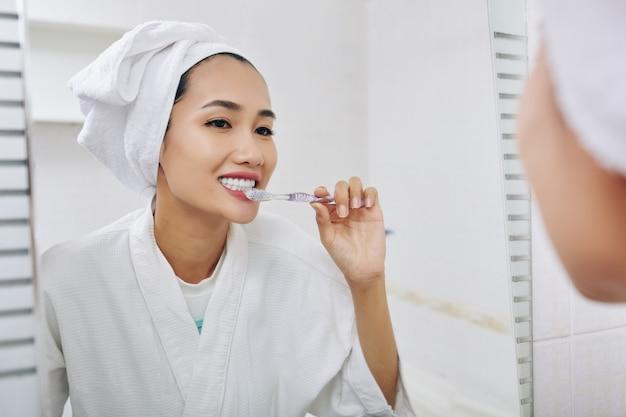 Piuttosto giovane donna vietnamita lavarsi i denti dopo aver fatto la doccia al mattino