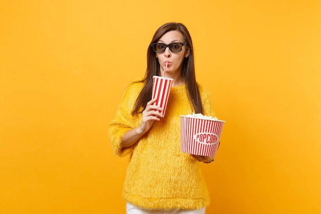 Bella giovane donna in occhiali 3d imax che guarda film film tenendo secchio di popcorn, bevendo cola o soda dal bicchiere di plastica isolato su sfondo giallo. persone sincere emozioni nel cinema, nello stile di vita.
