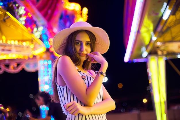 Bella giovane donna sullo sfondo di magiche luci carosello luminose.