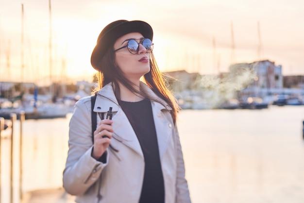 Giovane donna graziosa in cappello nero con vape ad un porto marittimo