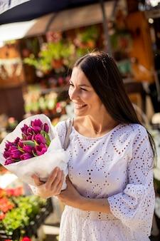 Bella giovane donna che compra fiori al mercato dei fiori