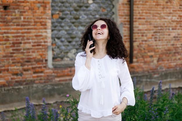 Primo piano abbastanza giovane della donna in maglione arancione che parla sul telefono cellulare. ritratto all'aperto.