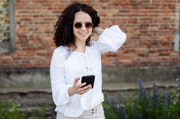Primo piano piuttosto giovane donna in bianco guardando il telefono cellulare, contro un edificio con sfondo di mattoni rossi.