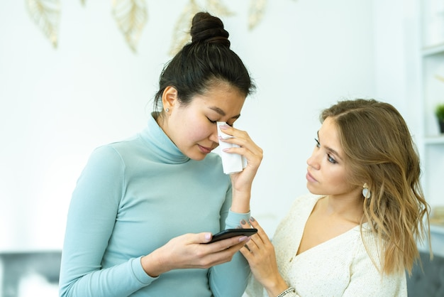 Donna abbastanza giovane che conforta il suo amico sconvolto che piange dopo aver ricevuto un cattivo messaggio sullo smartphone