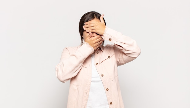 Bella giovane donna che copre il viso con entrambe le mani dicendo no alla telecamera! rifiutare le foto o vietare le foto