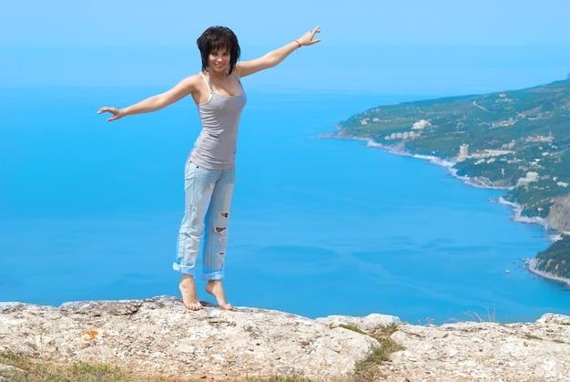 Bella giovane donna che balla sulla roccia
