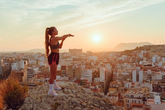 La donna abbastanza giovane fa yoga con vista sulla città al tramonto all'aperto