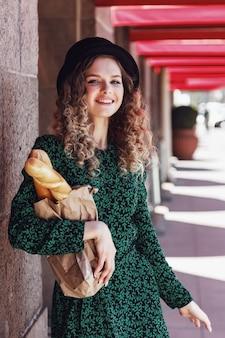 Piuttosto giovane donna vestita in stile francese con baguette in mano. stile femminile francese parigi. primo piano in abiti eleganti che tengono baguette di pane fresco e sorridono. copia spazio per sito o banner