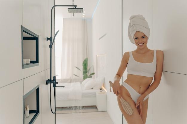 Bella giovane donna vestita in biancheria intima bianca che fa massaggio alle gambe asciutte con spazzola organica in legno dopo aver fatto la doccia mattutina in bagno all'interno dell'appartamento moderno. concetto di bellezza e cura del corpo delle donne