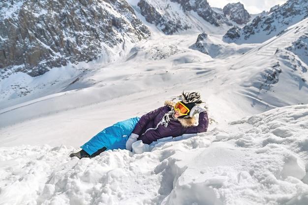 Bella giovane donna vestita con abiti invernali, occhiali e buffo cappello invernale sdraiato sulla montagna di neve
