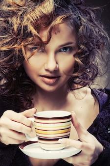 Bella giovane donna che beve caffè