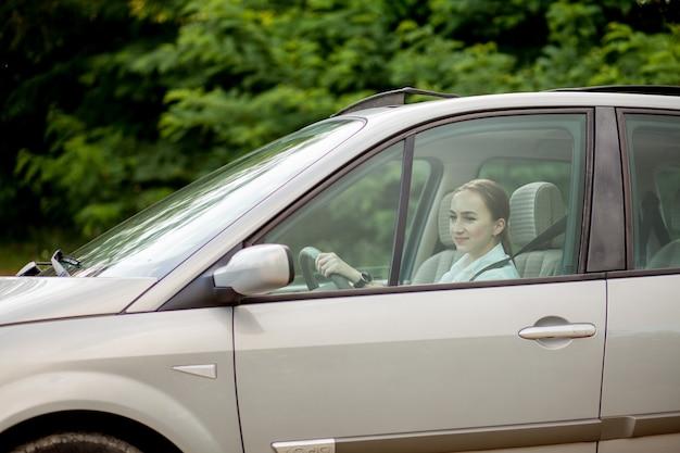Bella, giovane donna alla guida di un'auto - invito a viaggiare. noleggio auto o vacanza.