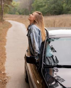 Donna abbastanza giovane che gode del viaggio su strada