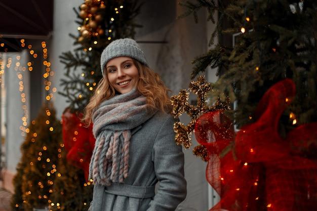 Bella giovane donna in abiti eleganti lavorati a maglia vintage alla moda vicino a luci gialle in città durante le vacanze