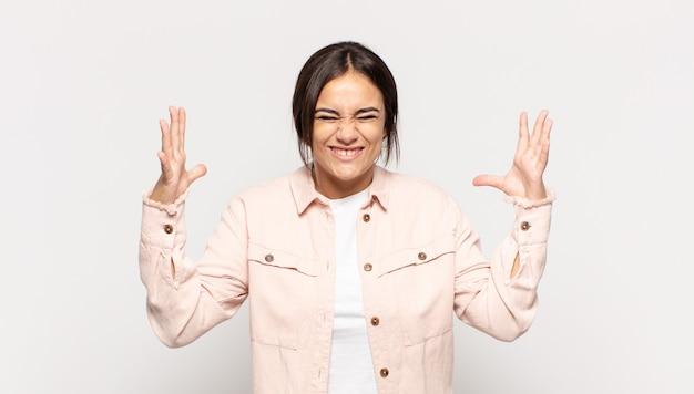 Piuttosto giovane donna che urla furiosamente, sentendosi stressata e infastidita con le mani in alto che dicono perché io