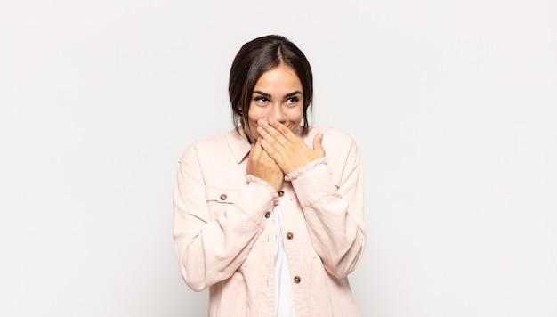 Bella giovane donna felice ed eccitata, sorpresa e stupita che copre la bocca con le mani, ridacchiando con un'espressione carina