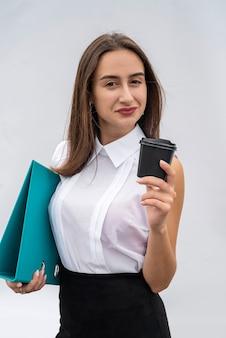 La cartella della tazza della tenuta della giovane donna graziosa indossa la camicia bianca e la gonna nera isolate.