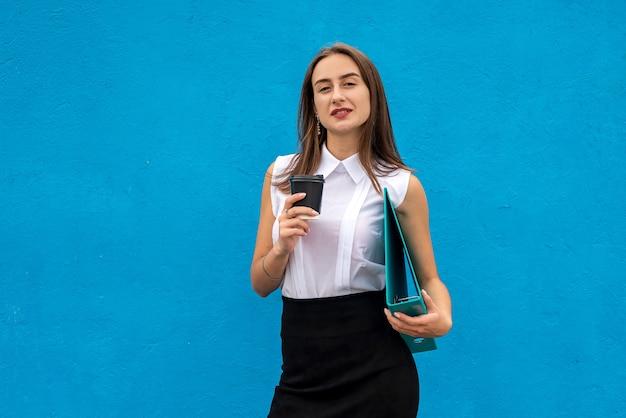 La cartella della tazza della stretta della donna abbastanza giovane indossa la camicia bianca e la gonna nera isolata
