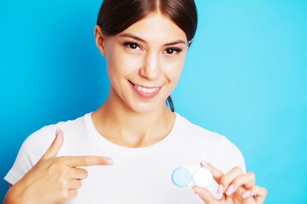Giovane donna graziosa che tiene un contenitore con le lenti a contatto per vista