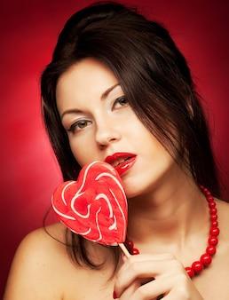 Piuttosto giovane donna con lecca lecca pop. su sfondo rosso.