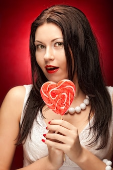 Piuttosto giovane donna con lecca-lecca pop. su sfondo rosso.