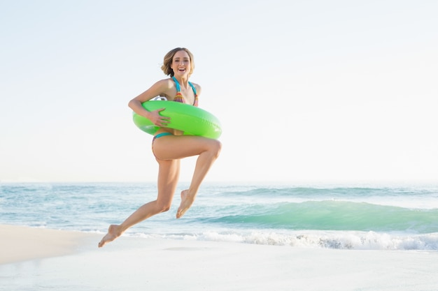 Giovane donna graziosa che tiene un anello di gomma mentre saltando sulla spiaggia